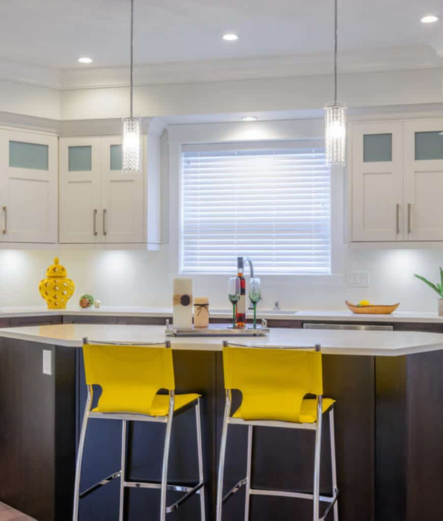 Fabulous kitchen accented with a yellow vase and counter chairs that sit at a dark wood breakfast bar lighted by cylindrical pendants and recessed lights.
