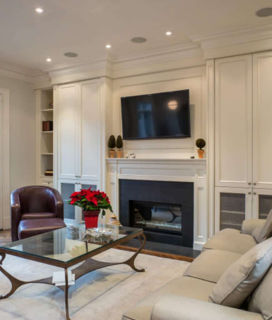 White living room offers a stylish coffee table accompanied with a leather round back chair and gray sectional. There's also a television and fireplace fitted in the middle of the built-in cabinets.