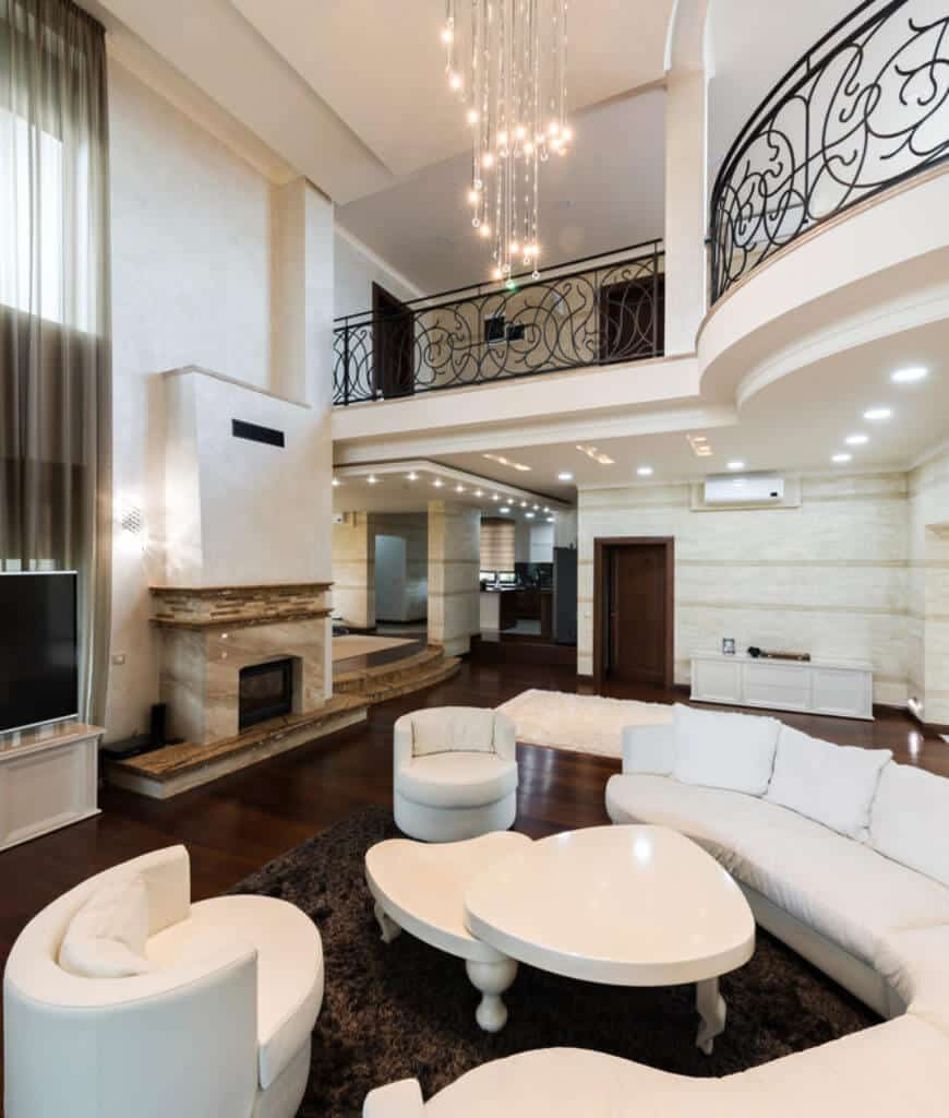 Contemporary living room boasts a marble fireplace along with a curved sofa and round back chairs surrounding a modular coffee table lighted by a cascading crystal chandelier.