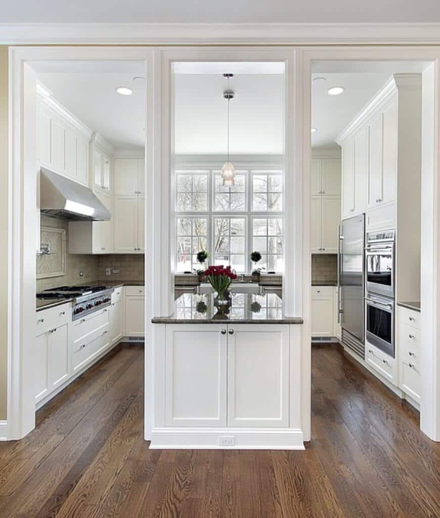 Open doorways lead to this kitchen filled with white cabinetry and stainless steel appliances. It is illuminated by glass pendants along with natural light that flows through the white framed windows.