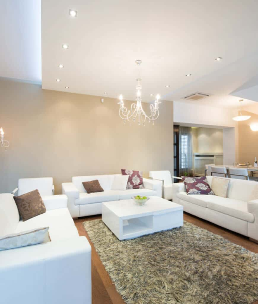 Sleek living room offers white seats and coffee table that sits on a shaggy rug lighted by a chrome chandelier and recessed ceiling lights.