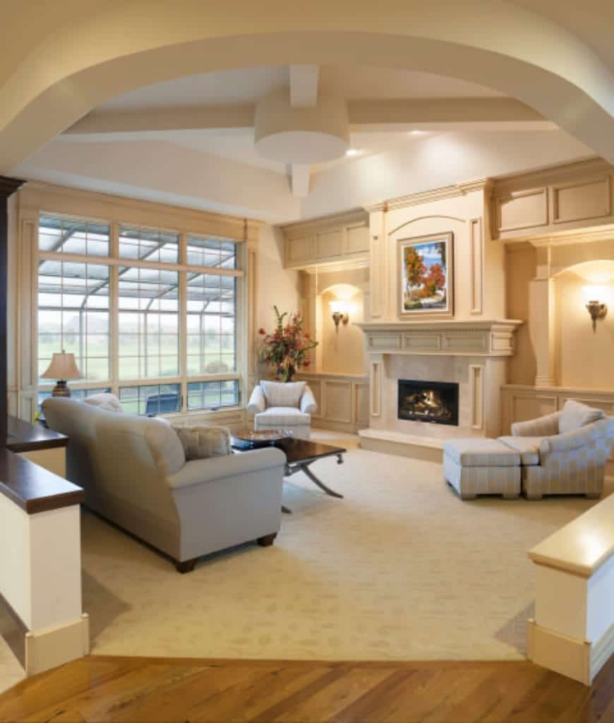 A lovely wall art hangs above the fireplace in this living room with arched inset walls mounted with sconces and framed with wainscoting.