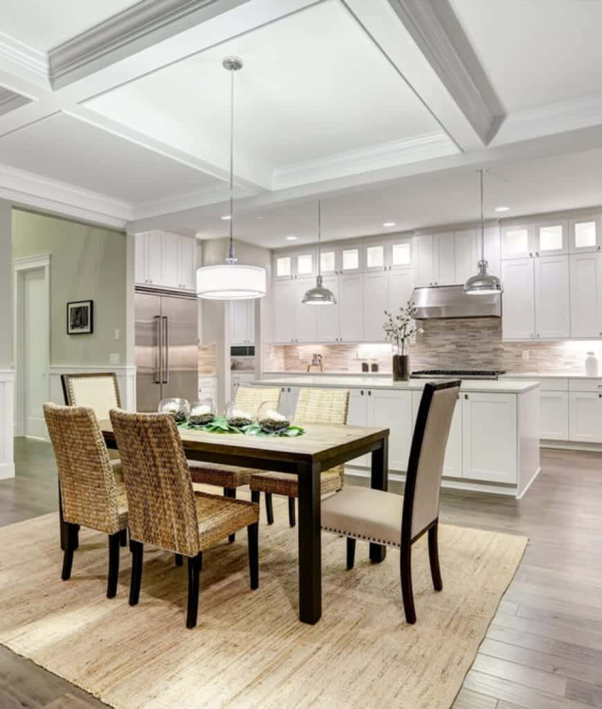 Dine-in kitchen with white coffered ceiling and natural wood plank flooring topped by an area rug. It includes a rustic dining set paired with wicker and beige high back chairs.