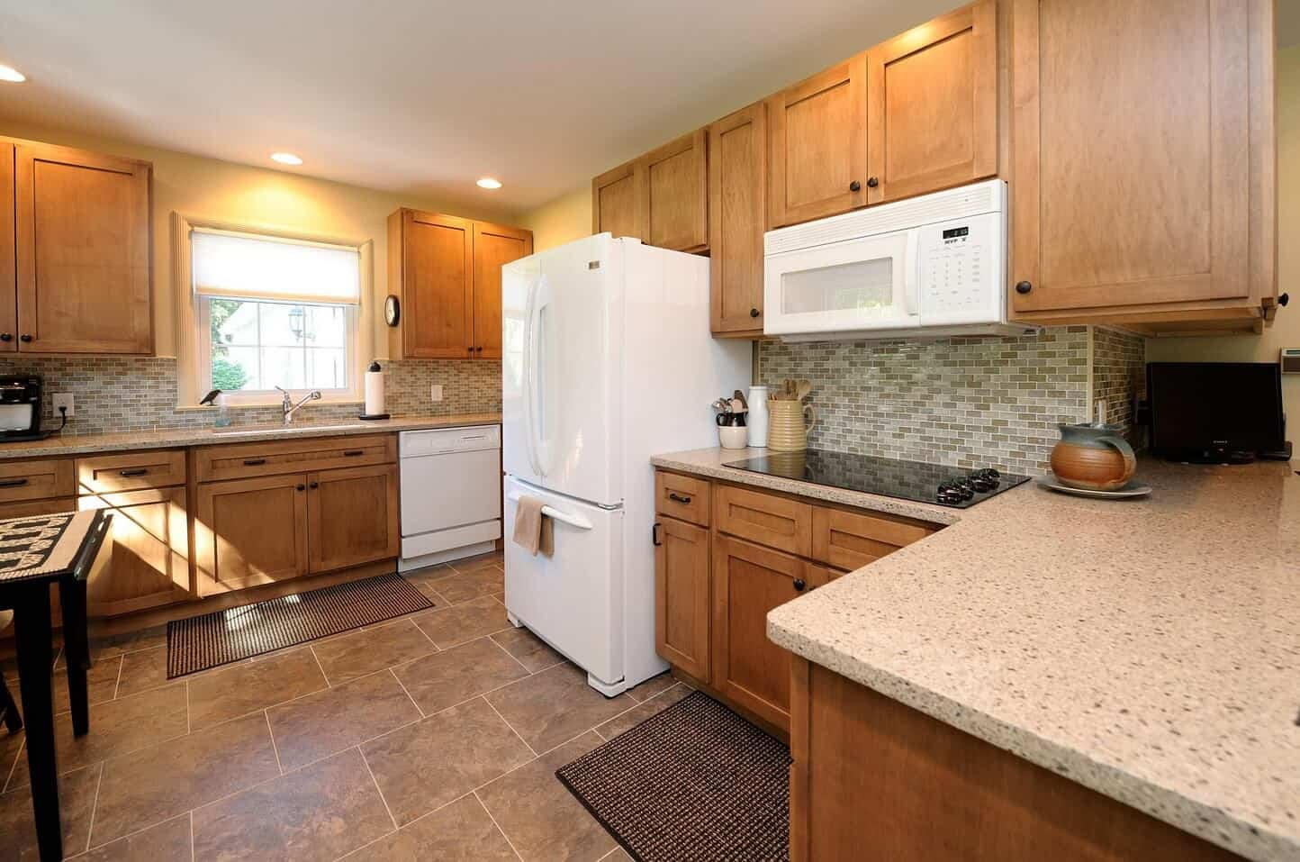 Warm kitchen with white fridge and microwave suspended over the induction cooktop mounted on the granite countertop. It is surrounded with wooden cabinetry and stylish mosaic backsplash tiles.