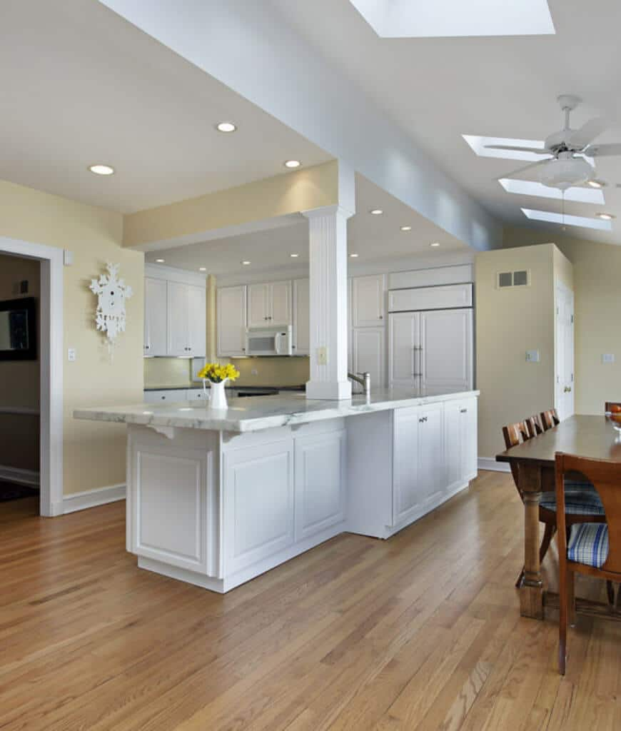 Recessed ceiling lights illuminate this kitchen along with skylights fixed to the vaulted ceiling. It has white cabinetry and appliances along with a kitchen counter lined with a white column.