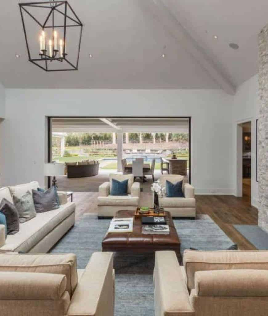 Velvet pillows lay on the beige seats in this living room illuminated by a caged chandelier and recessed lights mounted on the vaulted ceiling.