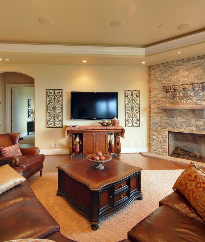 Yellow living room decorated with ornate wall arts highlighting the television in the middle. It has a leather wingback chair and curved sectional surrounding the wooden coffee table on a beige textured rug.