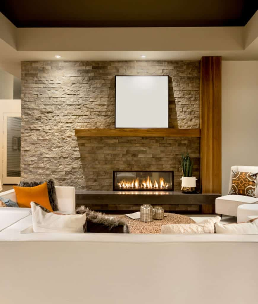 This living room showcases white seats and a modern fireplace fixed to the stone brick accent wall lined with a wooden mantel that's topped with a black canvas.