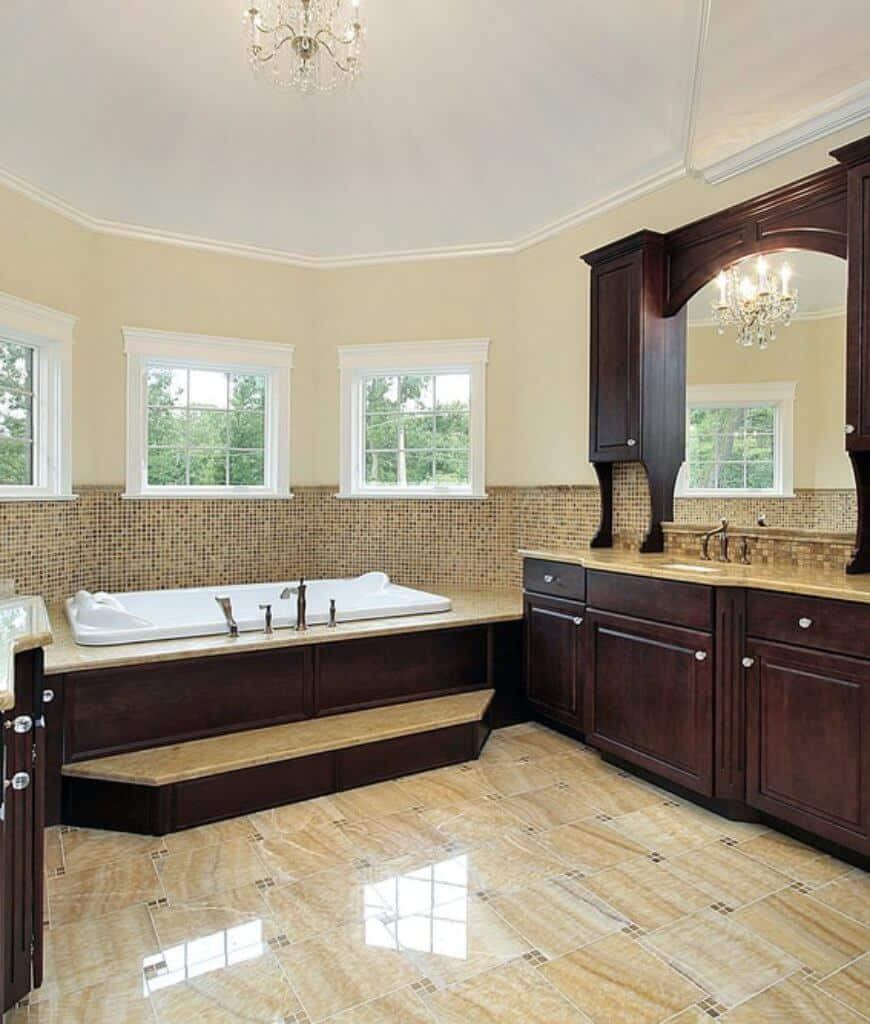 Sophisticated master bathroom offers a wooden sink vanity and a soaking bathtub accented with gold mosaic tiles clad beneath the white framed windows.