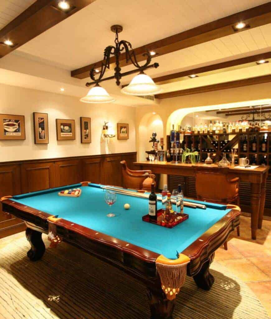 Warm man cave decorated with a series of framed wall arts mounted above the wooden wainscoting. It has a bar area and a pool table illuminated by wrought iron pendants.