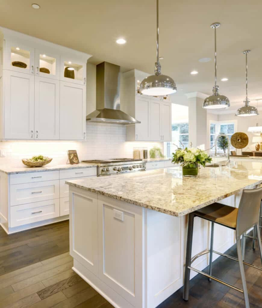 Bright kitchen offers white cabinetry and a matching breakfast island lighted by chrome pendants and recessed ceiling lights.