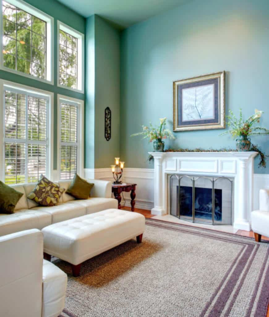 An aqua living room boasts a fireplace framed with white mantel and metal fence fixed to the white wainscoting. It has a leather tufted sofa set that sits in a woven rug over hardwood flooring.