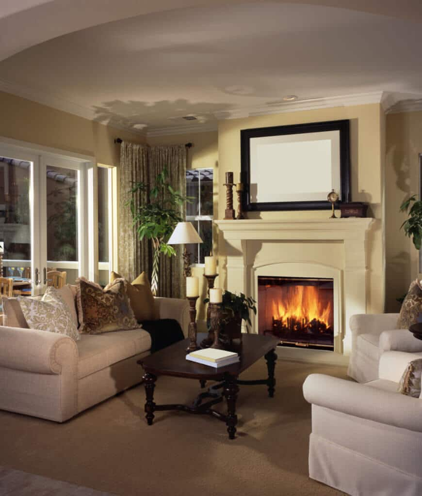 Tropical living room features beige sofa and armchairs paired with a dark wood coffee table that sits on a tan rug. It includes a fireplace topped with candles and a black framed wall art.