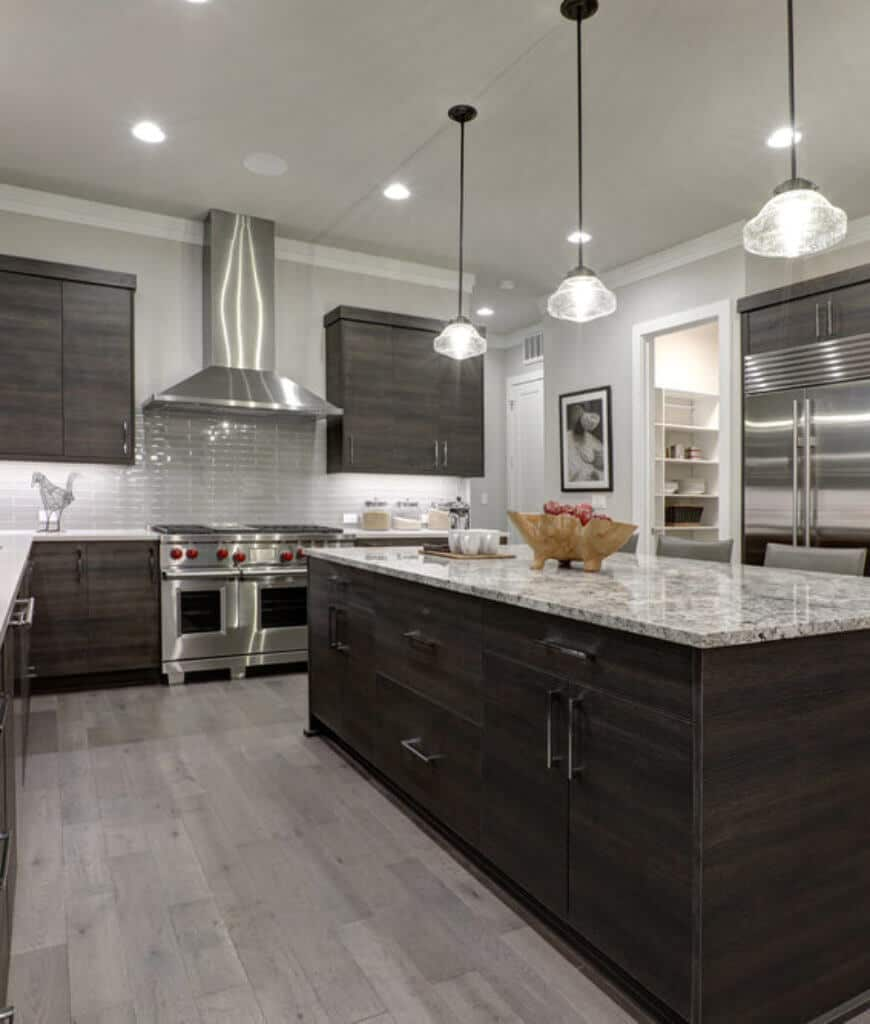 Gourmet kitchen decorated with black framed wall art and glass pendants that hung over the dark wood island bar topped with a marble counter and stylish bowl.