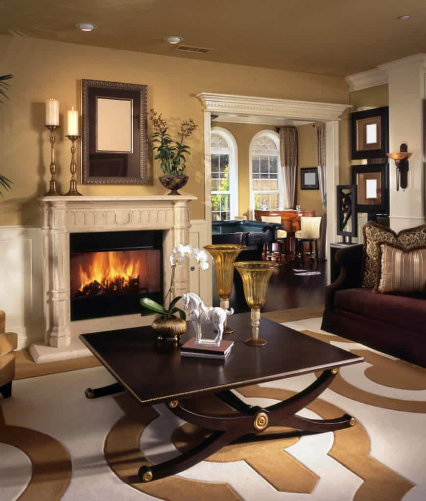 This living room showcases a smooth dark wood coffee table on a patterned rug and a fireplace that's framed with ornate mantel and fixed on the white wainscoting.