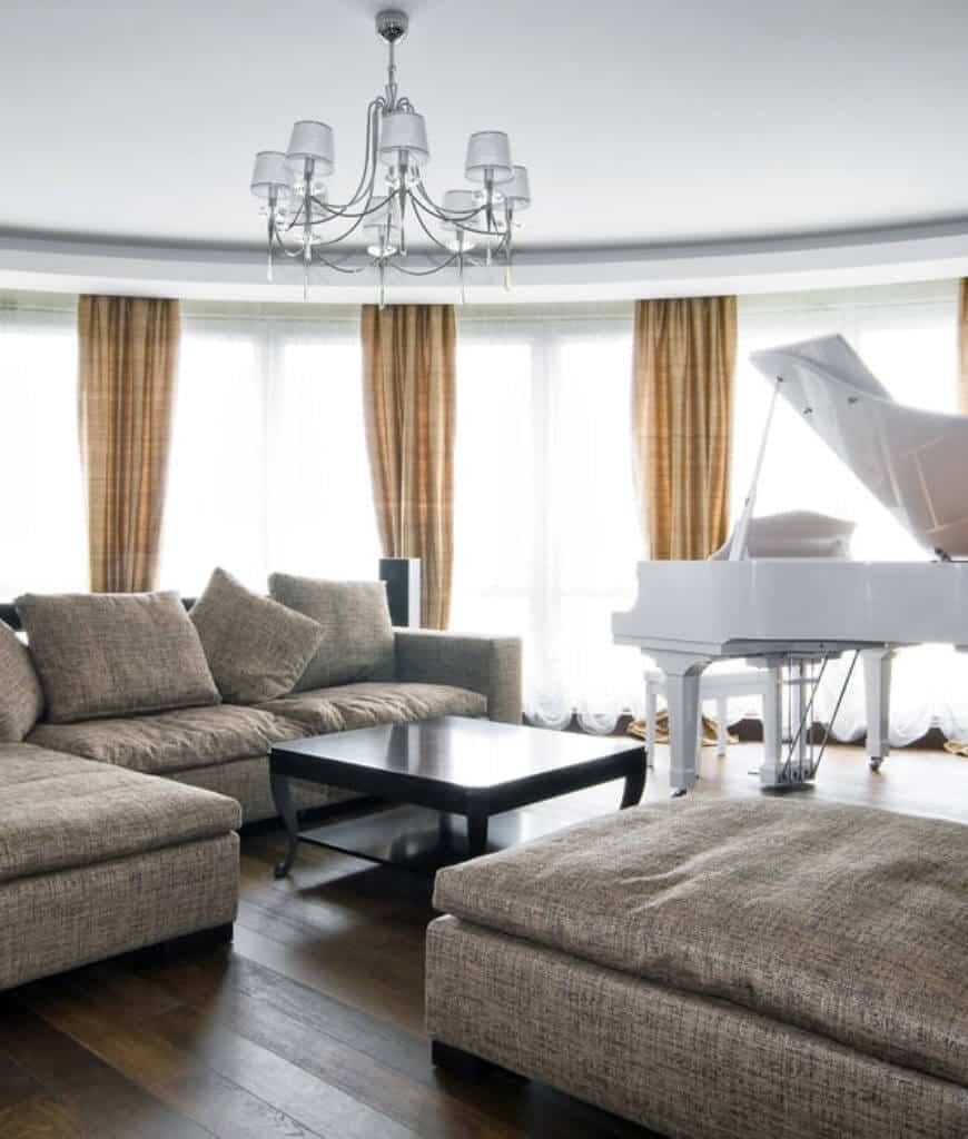 Bright living room features natural wood plank flooring and full height windows covered with tan draperies. It includes gray sectional and ottoman accompanied by a black coffee table and a white baby grand piano.