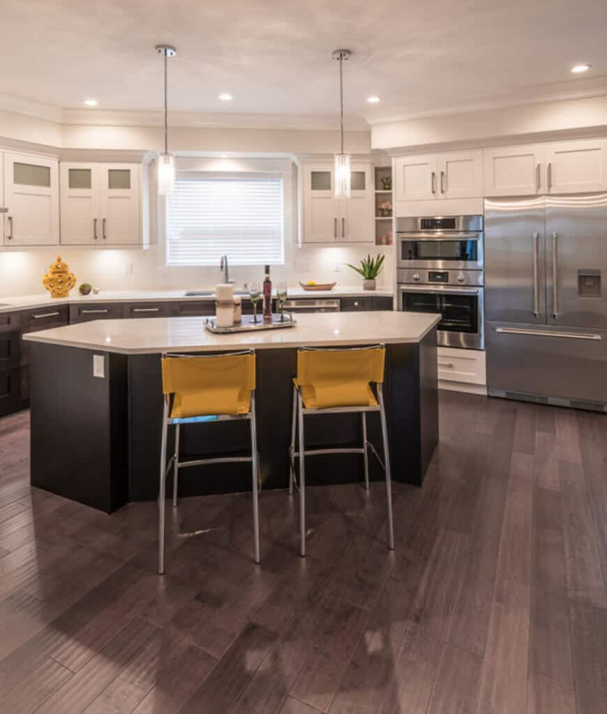 Fabulous kitchen accented with a yellow vase and counter chairs that sit at a hexagonal breakfast bar lighted by cylindrical pendants and recessed lights.