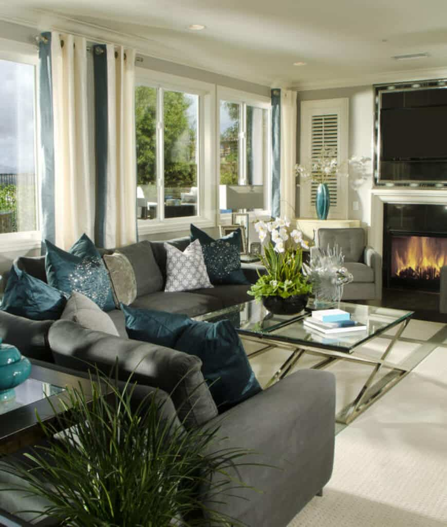 Gorgeous living room with glass top coffee table and L-shaped sectional filled with classy pillows. It includes a fireplace ad glass paneled windows covered with cream draperies.