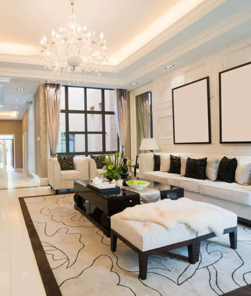 A fancy chandelier that hung from the tray ceiling illuminates this glam living room with dark wood coffee table and cozy seats filled with black and gray pillows.