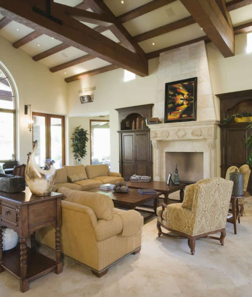 A black framed wall art hangs above the fireplace in this living room with marble flooring and vaulted ceiling framed with natural wood beams.