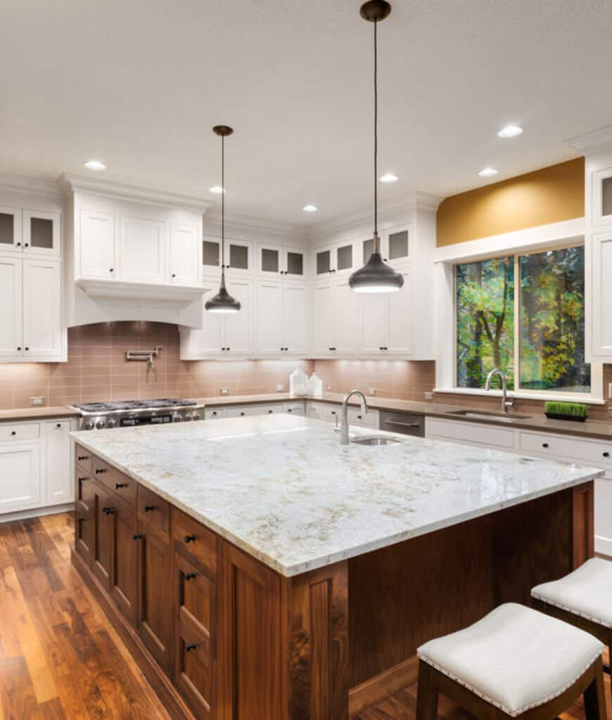 This kitchen boasts an immense breakfast island lighted by a pair of black pendants and surrounded with white cabinetry and cushioned bar stools.