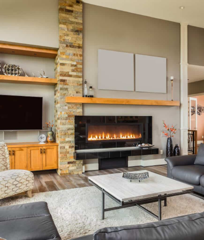A pair of blank canvases are mounted above the wooden mantel in this living room showcasing a modern fireplace fixed to the gray wall that's lined with a stone brick column.