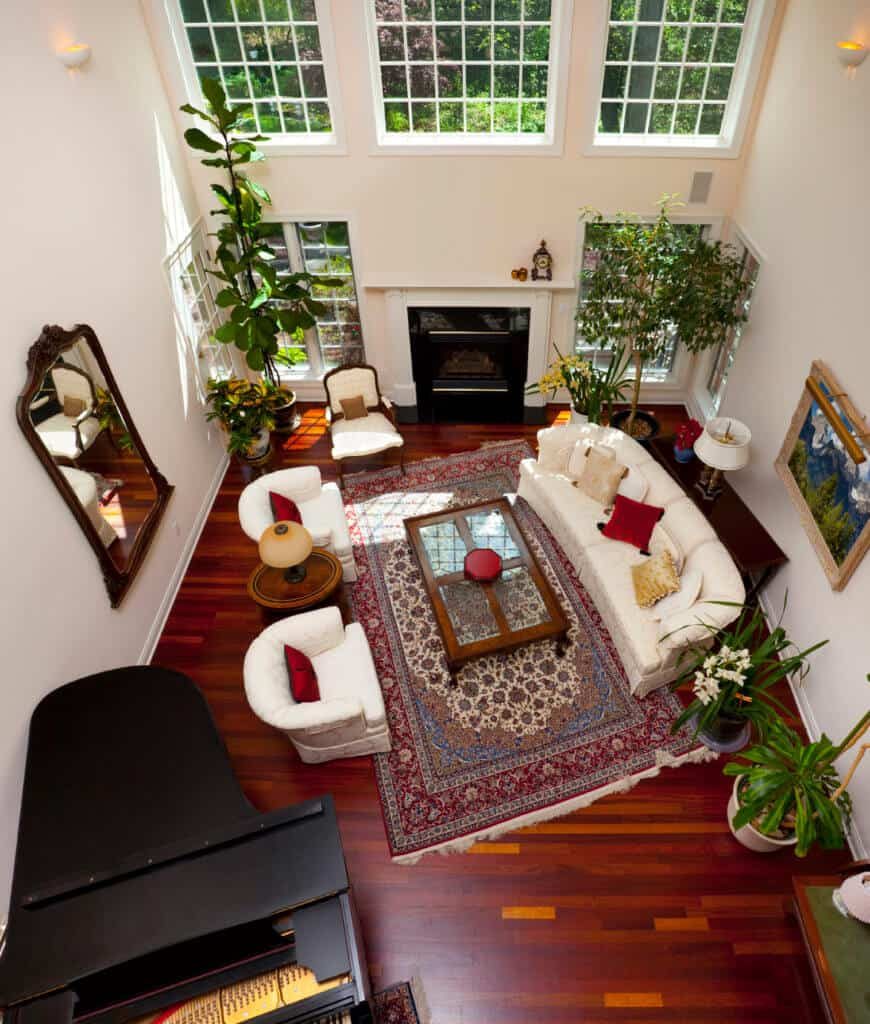 Fabulous living room with high ceiling and rich hardwood flooring topped by a red vintage rug. It has a glass top coffee table and white round back seats accented with red pillows.