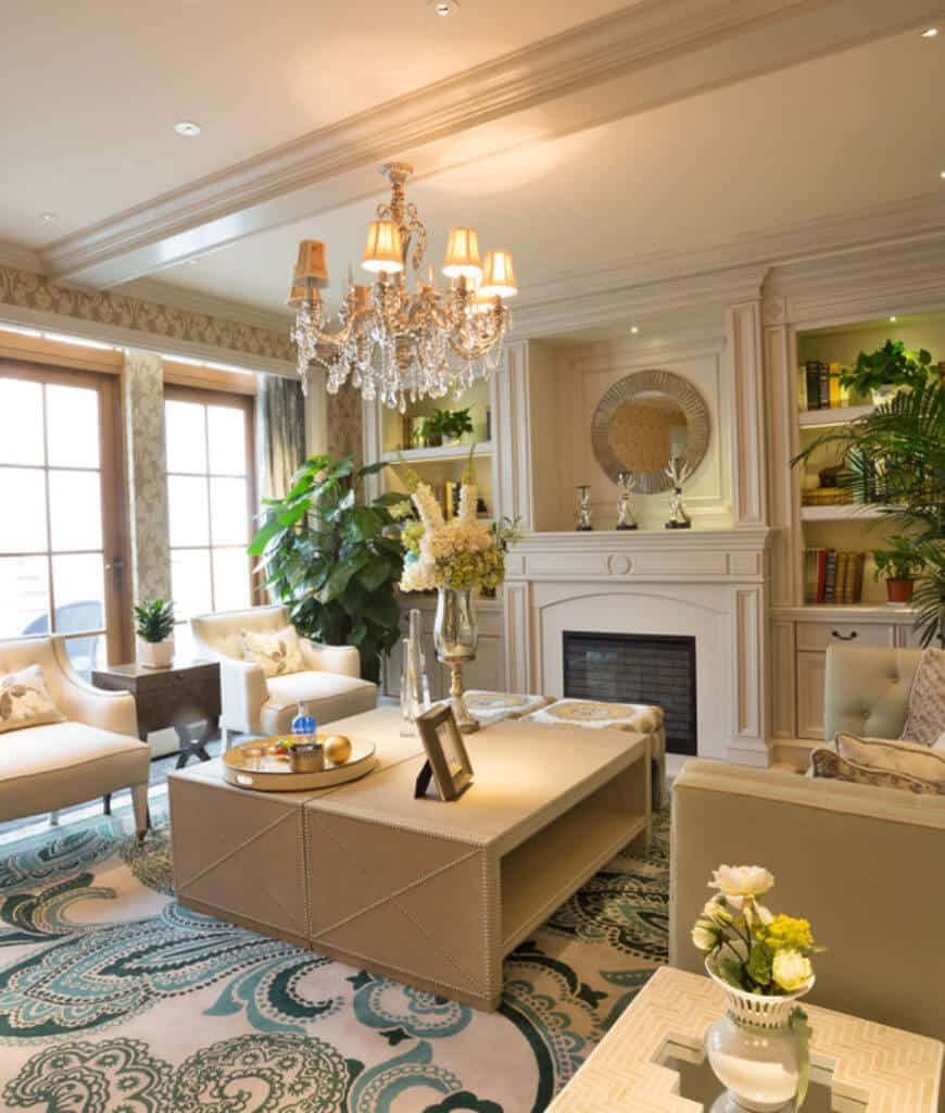 Victorian living room boasts tufted seats and a coffee table lighted by a fancy chandelier. It includes a fireplace topped with chrome decors and a round mirror.