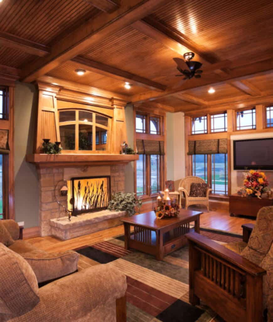 An all wood living room boasts a stone fireplace enclosed in glass along with comfy chairs and sofa surrounding a wooden coffee table that sits on a multi-colored striped rug.