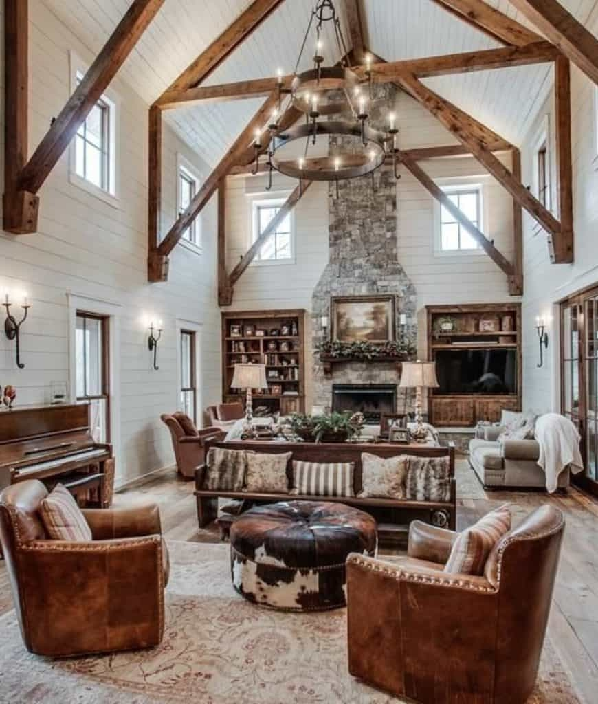 A wrought iron chandelier that hung from the cathedral ceiling framed with wood beams illuminates this rustic living room showcasing a stone fireplace and multiple seating areas.