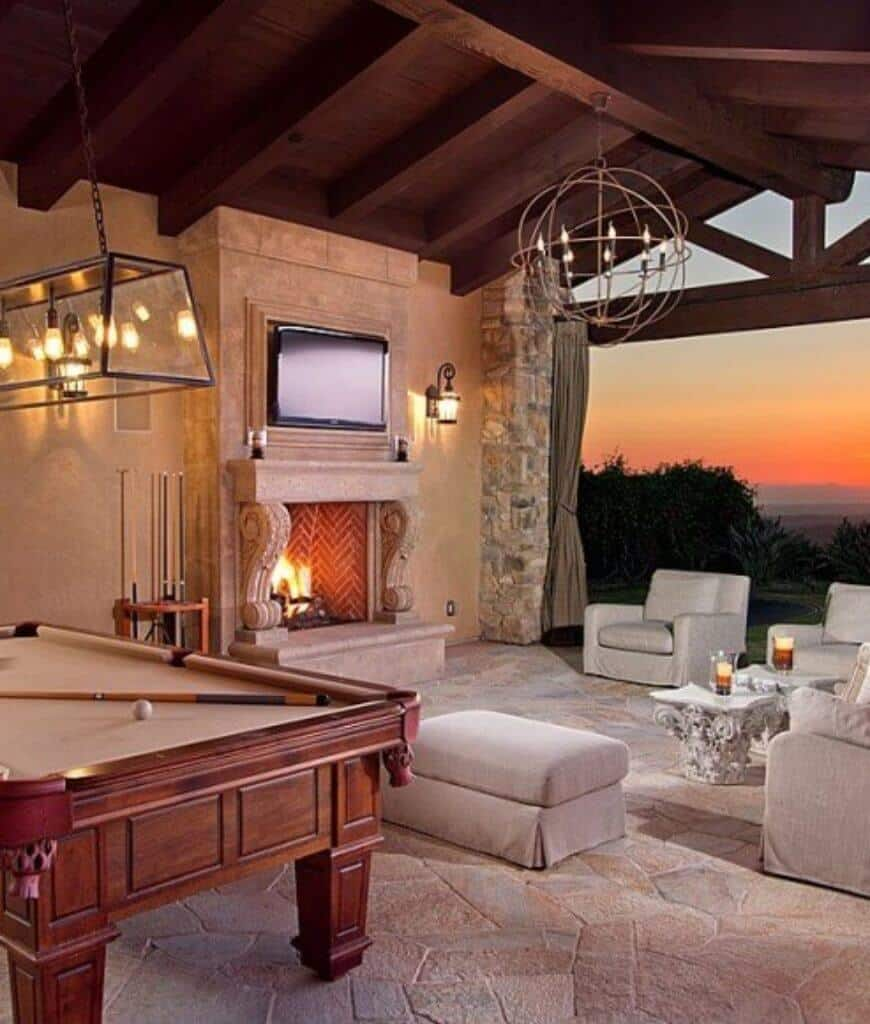 An open entertainment room with gray skirted seats surrounding the ornate coffee tables and chevron fireplace with a television on top. It includes a wood paneled pool table on the side lighted by industrial pendant.