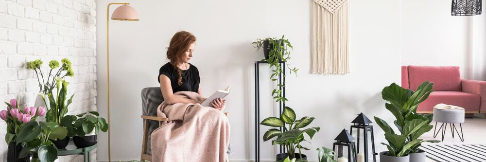 A woman reading a book in a lovely room.