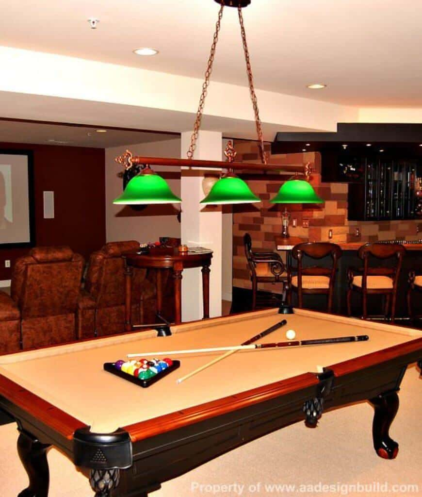Green pendant lights stand out in this entertainment room filled with bar counter and pool table situated behind the leather sectional and round wooden table.