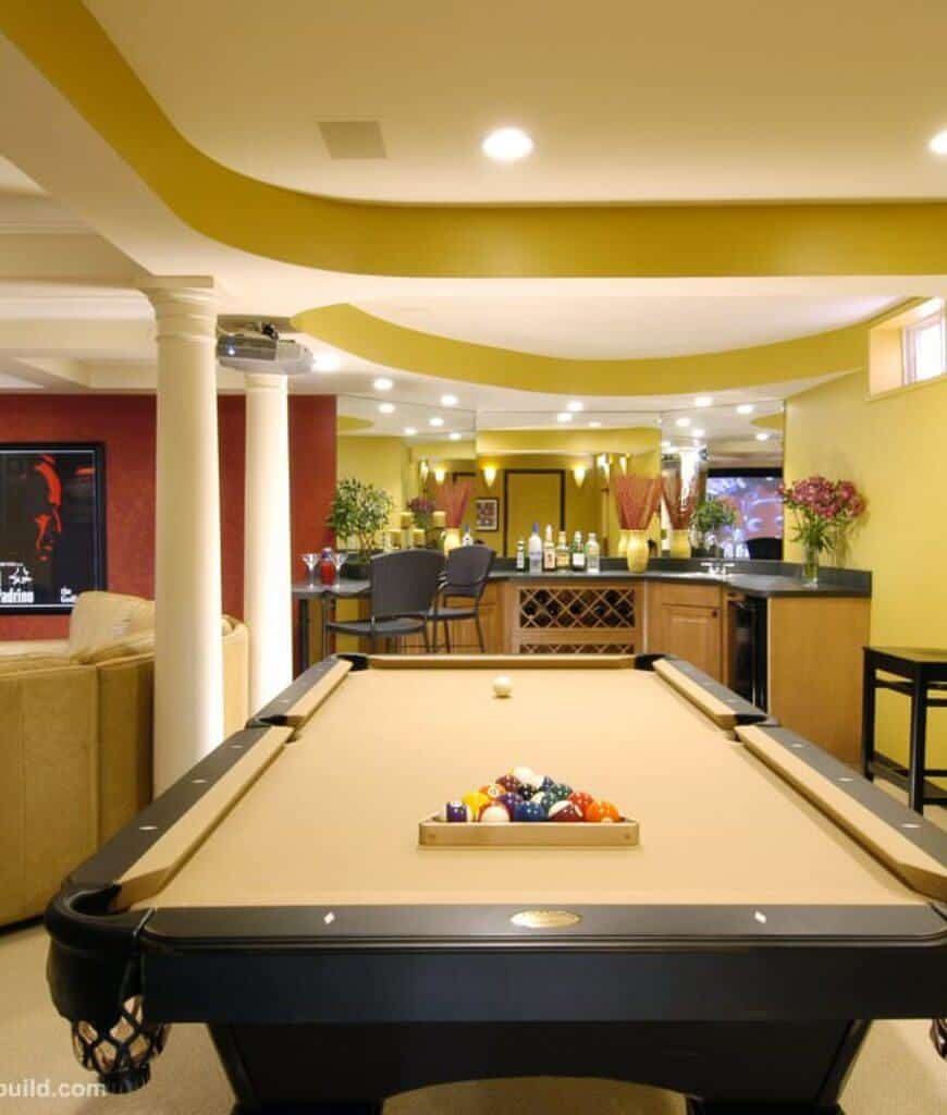 Deluxe entertainment room with a living space next to the curved bar area facing the yellow pool table that's lined with white columns.