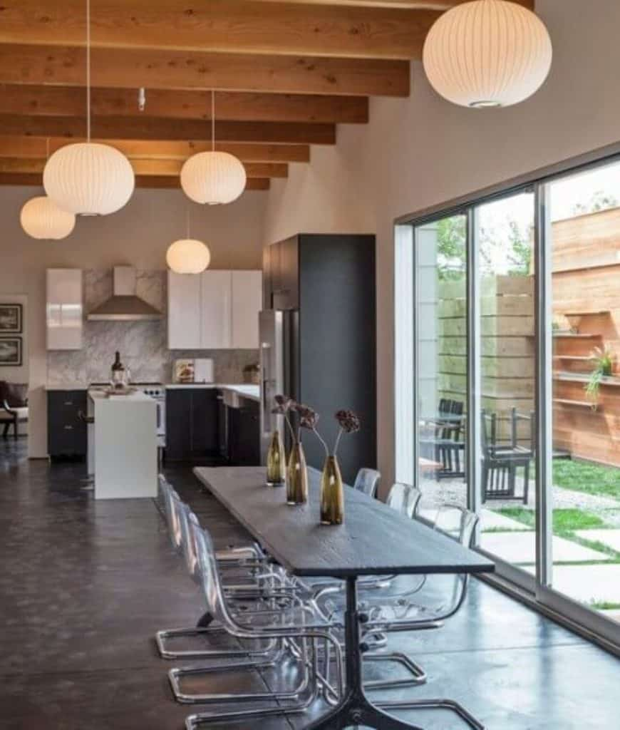 Long and narrow eat-in kitchen furnished with a black dining table and glass chairs lighted by round pendants that hung from the wood beam ceiling. It has concrete flooring and glass slider that leads to the lush green yard.