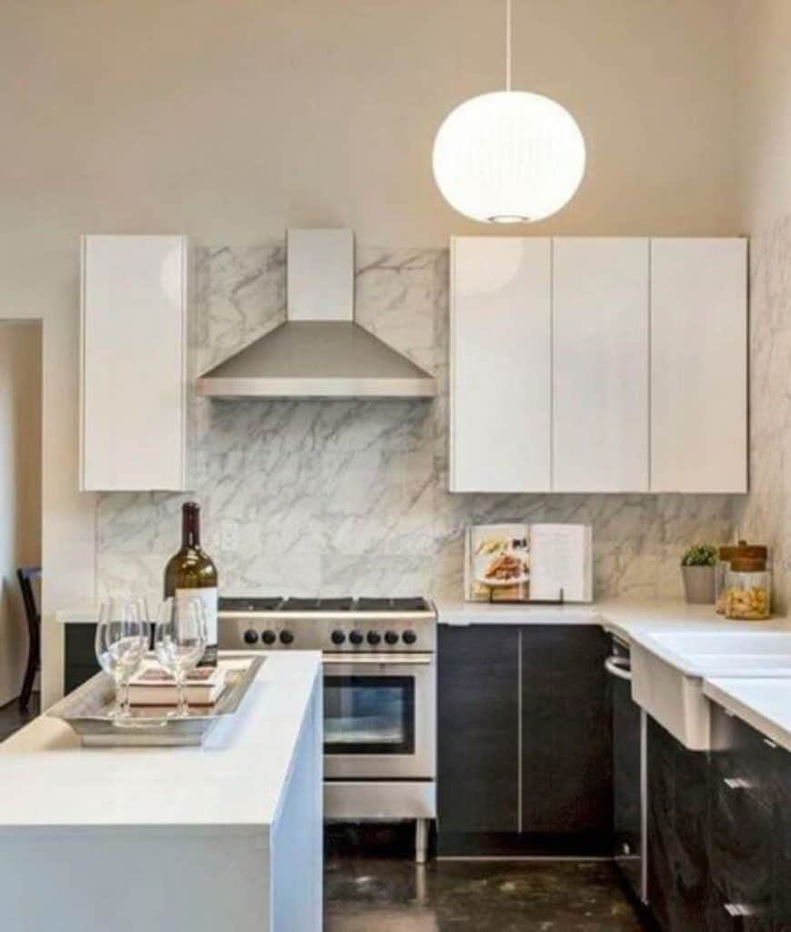 Small kitchen lighted by a round pendant offers sleek cabinetry and stainless steel vent hood fixed on the marble backsplash.