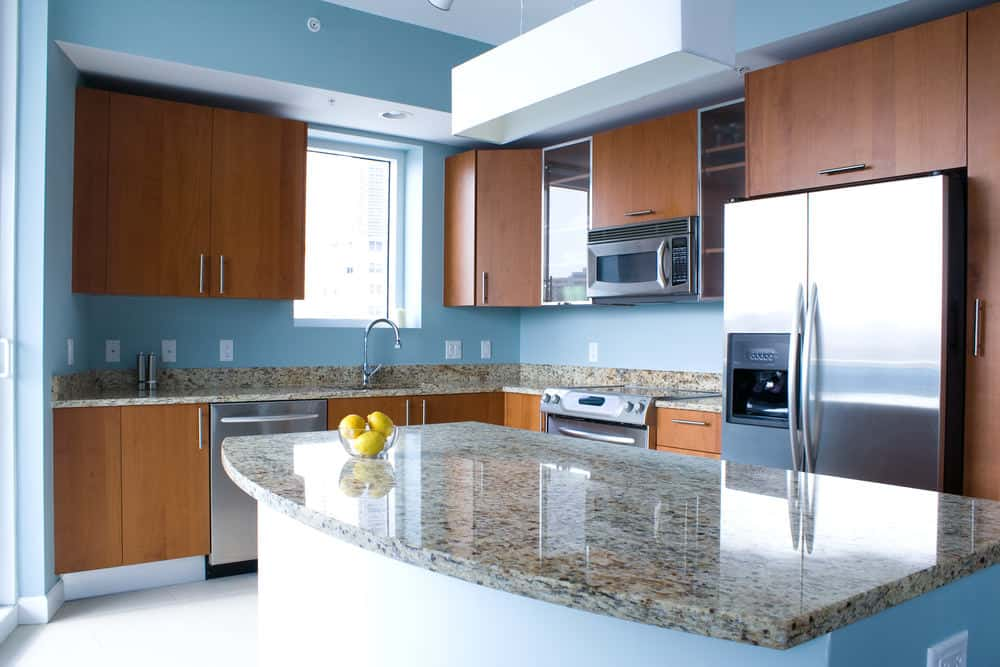 This kitchen features granite countertops on both kitchen counters and center island. The area has a light blue theme as well.