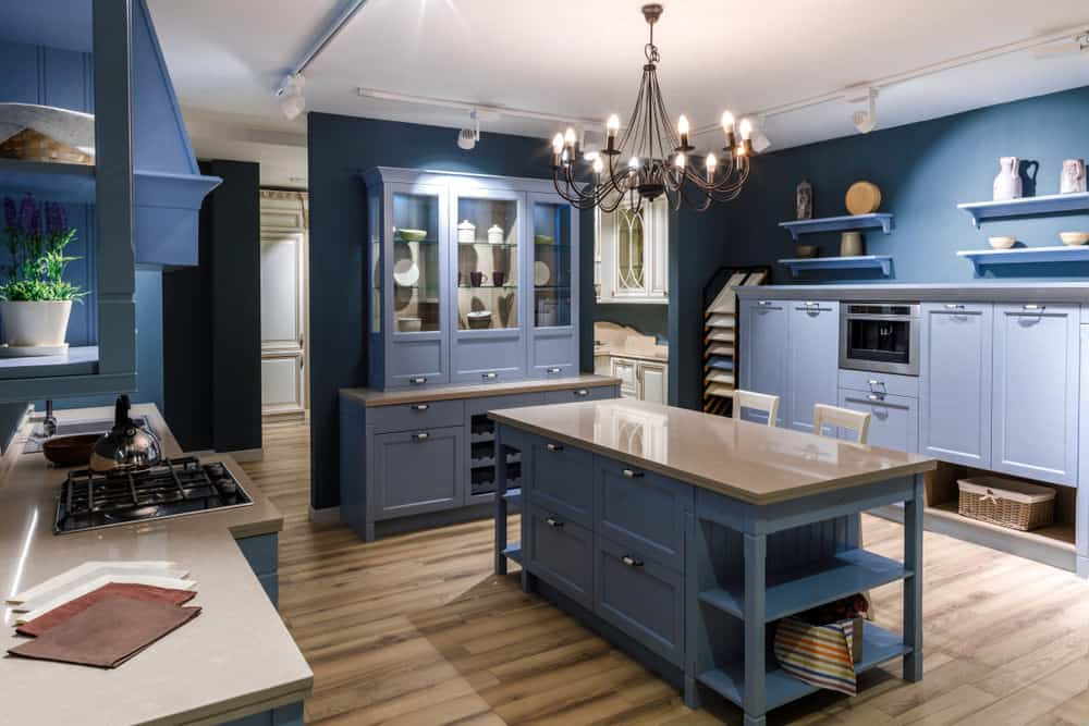 A kitchen featuring blue kitchen counters and cabinetry. The area has hardwood flooring and a white ceiling with a gorgeous chandelier.