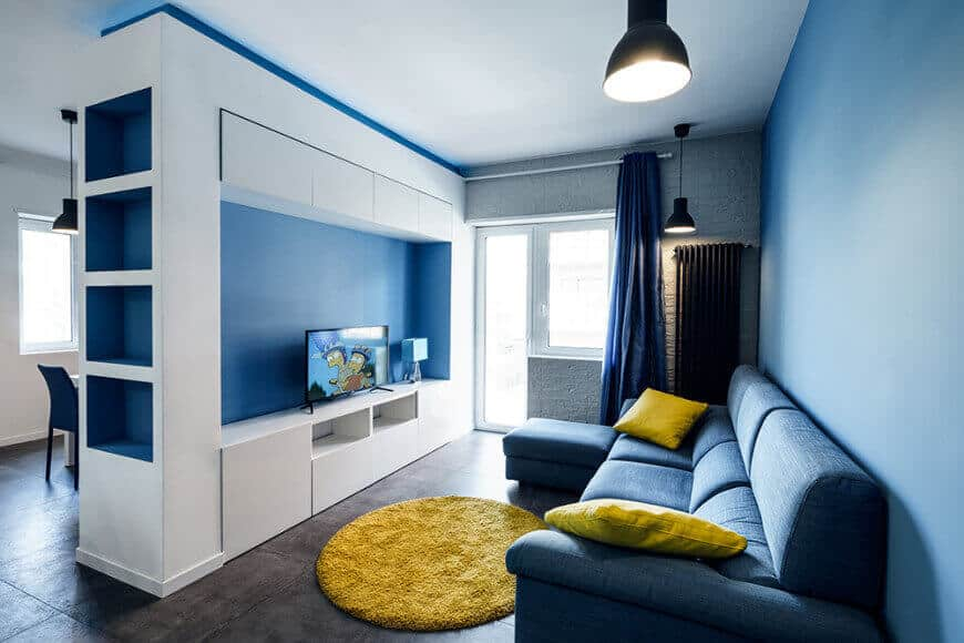 Small living space featuring a blue couch matching the blue walls and blue window curtain. The yellow accent looks attractive too.
