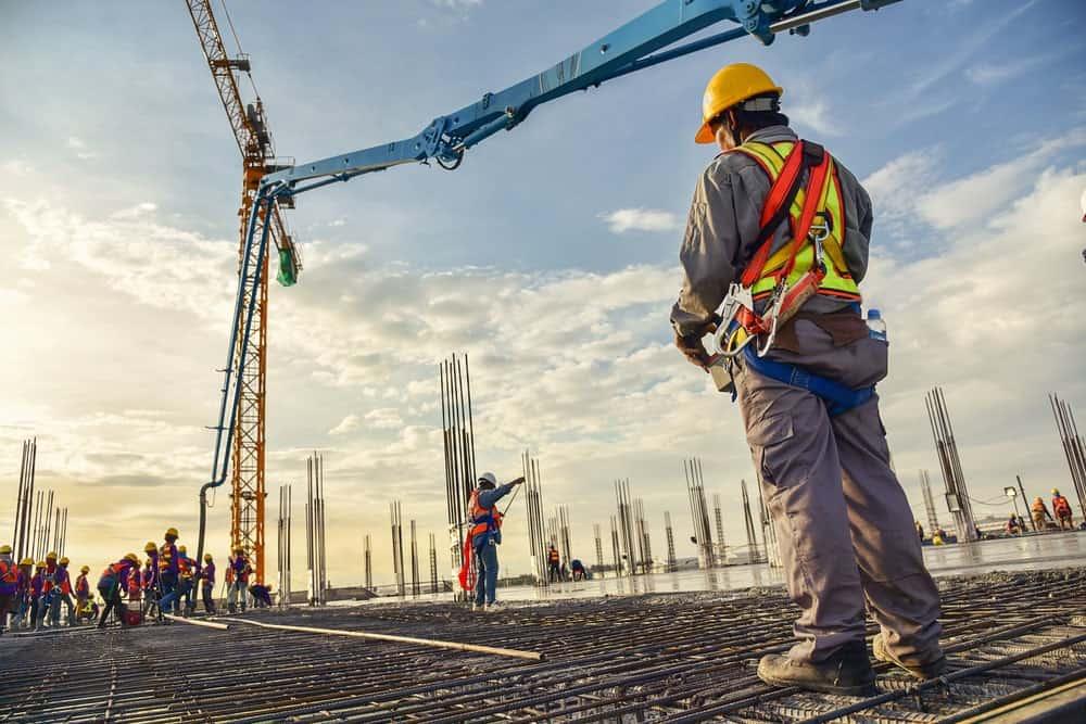 A construction worker controlling a pouring concrete pump on construction site