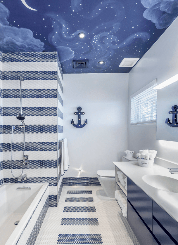 A nautical-themed master bathroom featuring stylish walls and floors, along with a shower and tub combo and a smooth sink counter.
