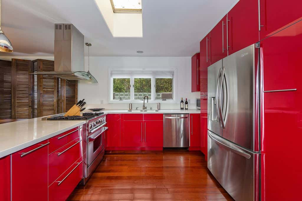This kitchen features red kitchen counters and cabinetry, along with white countertops and hardwood flooring.