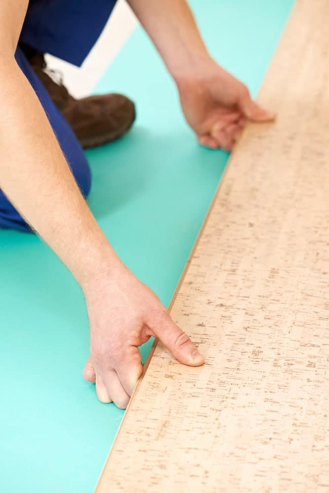 Carpenter installing cork flooring tiles