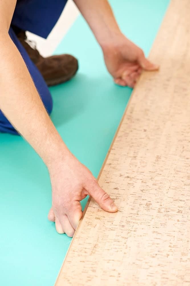 Carpenter installing cork flooring tiles