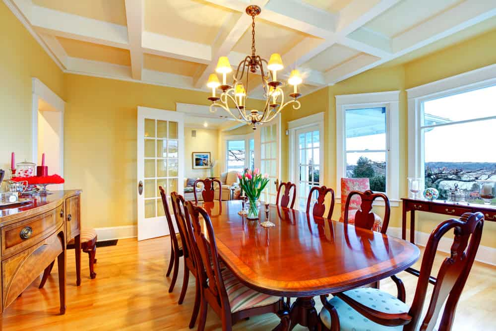 Dining room with coffered ceiling, chandelier, white trimmed windows and French doors, and yellow walls.