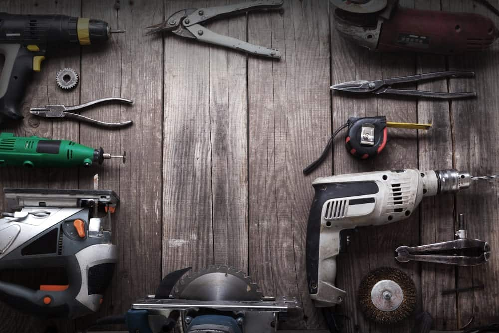 A set of hand tools on a black wooden table.