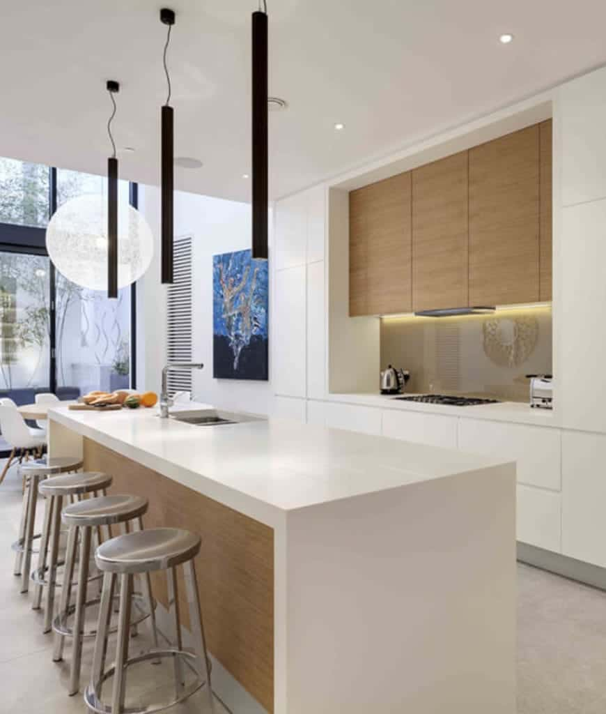 Modern eat-in kitchen decorated with a lovely wall art along with spherical and black cylindrical pendants that hung over the island bar lined with chrome bar stools.