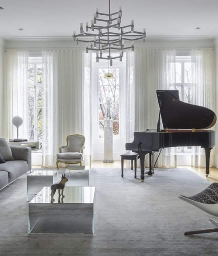 Airy living room features a unique chandelier and mirrored cube coffee tables accompanied with gray seats and a baby grand piano by the white framed windows.