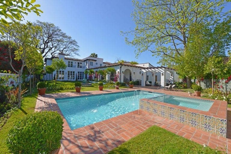 A spacious backyard with an elegant pool in the midst of a relaxing scenery that complements the white walls, large French windows and arched entryways. These structures offer an almost unobstructed commune with the lavish landscape illuminated by the wall-mounted lamps on the outer walls of the Spanish-style mansion.