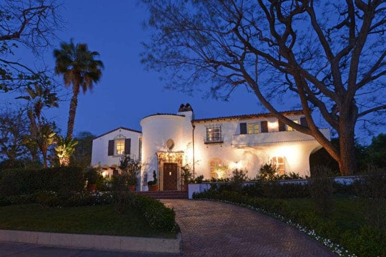 This Spanish-style mansion has bright white walls and clay tile roofing partnered with French windows and dramatic warm yellow light. It features an impressive stone walkway surrounded by abundant landscaping leading to a massive turret-shaped entrance hall that transitions to the traditional elegance of the house.